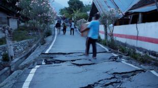 Moradores carregam o que podem pelo calçamento danificado pelo terremoto em Palu.
