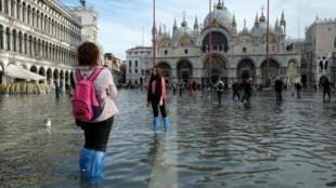 Turistas posam para fotos na Praça São Marco, inundada neste sábado (16/11/2019)
