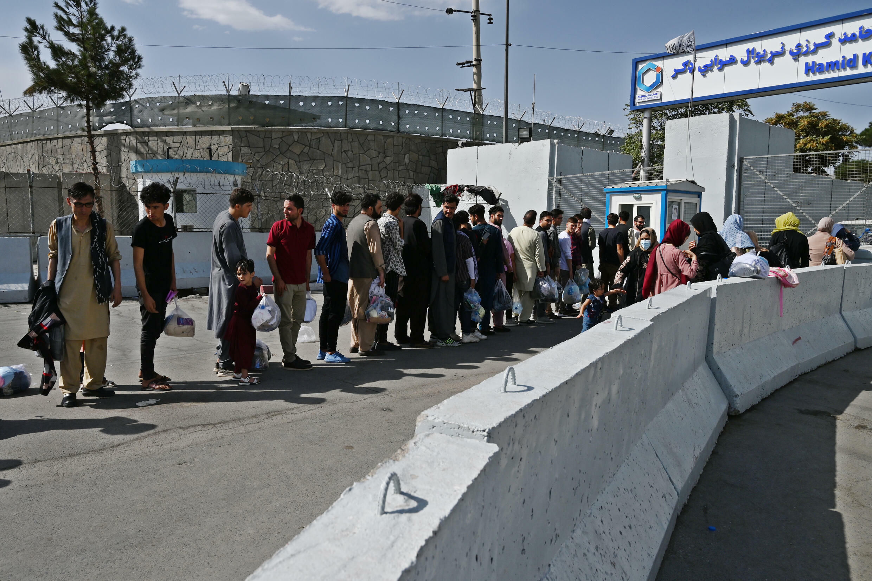 Afganos que quieren abandonar el país esperan delante de la entrada del aeropuerto de Kabul, el 29 de agosto de 2021