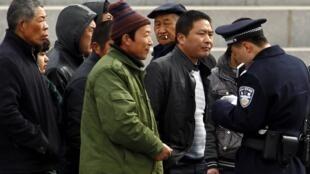 Công an Trung Quốc kiểm tra giấy tờ một người đi đường, tại khu vực bên ngoài Đại sảnh đường Nhân dân, ngày 08/03/2012.