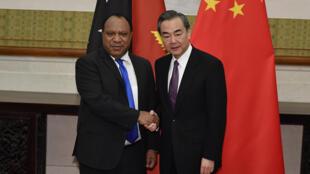 Ngoại trưởng Papua New Guinea Rimbink Pato (t) bắt tay ngoại trưởng Trung Quốc Vương Nghị trước buổi hội đàm tại Bắc Kinh (Trung Quốc) ngày 13/04/2018.