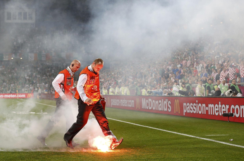 Персонал удаляет файеры с поля после матча Хорватия-Ирландия в Познани 10/06/2012