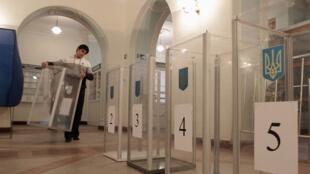 Un membre de la commission électorale locale transporte une urne dans un bureau de vote de Kiev, le 27 octobre 2012.