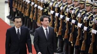 Os premiês Manuel Valls, Da França (à dir.) e Li Keqiang, da China, passam as tropas em revista neste 29 de janeiro de 2015.