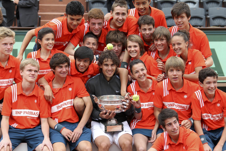 Rafael Nadal kutoka  Uhispania (katikati) akiwa na wavulana na wasichana wa baada ya sherehe ya kupewa tuzowakati wa michuano ya French Open, Juni 11, 2012