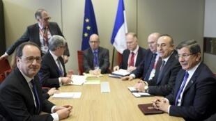 O presidente da França, François Hollande (esq.), junto com o primeiro-ministro turco, Ahmet Davutoglu (direita) e outros líderes durante cúpula da União Europeia em Bruxelas.