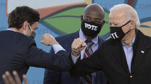 Os dois candidatos democratas às eleições do Senado americano, Jon Ossoff (a esquerda) e Raphael Warnock , (centro) com o presidente americano eleito Joe Biden, durante um comício em Atlanta, em 4 de janeiro de 2021.