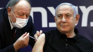 O primeiro-ministro israelense Benjamin Netanyahu recebe uma dose da vacina contra a Covid-19. O governo israelense anunciou um novo lockdown nesta quinta-feira, 24 de dezembro.