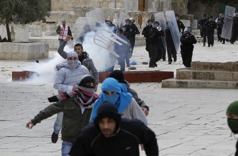 Manifestantes palestinos correm da polícia israelense durante confrontos na Esplanada das Mesquitas em Jerusalém nesta sexta-feira, dia 24 de fevereiro.