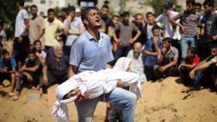 Un palestino carga el cuerpo de una niña fallecida durante un ataque israelí en el norte de Gaza, este 4 de agosto de 2014.