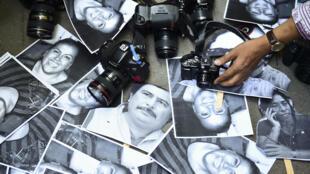 Unos periodistas dejan sus cámaras junto a unas fotografías de compañeros asesinados durante una protesta en el exterior de la oficina de representación del estado mexicano de Veracruz en Ciudad de México el 11 de febrero de 2016