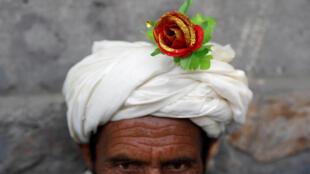Uma flor artificial é vista no turbante de um manifestante pela paz em Cabul, Afeganistão, em 18 de junho de 2018.