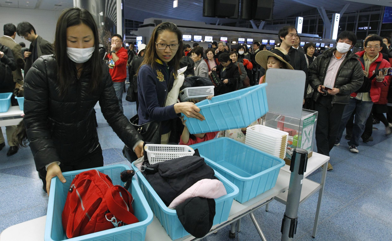 Passageiros que se preparam para deixar o Aeroporto de Tóquio a 17 de Março de 2011.