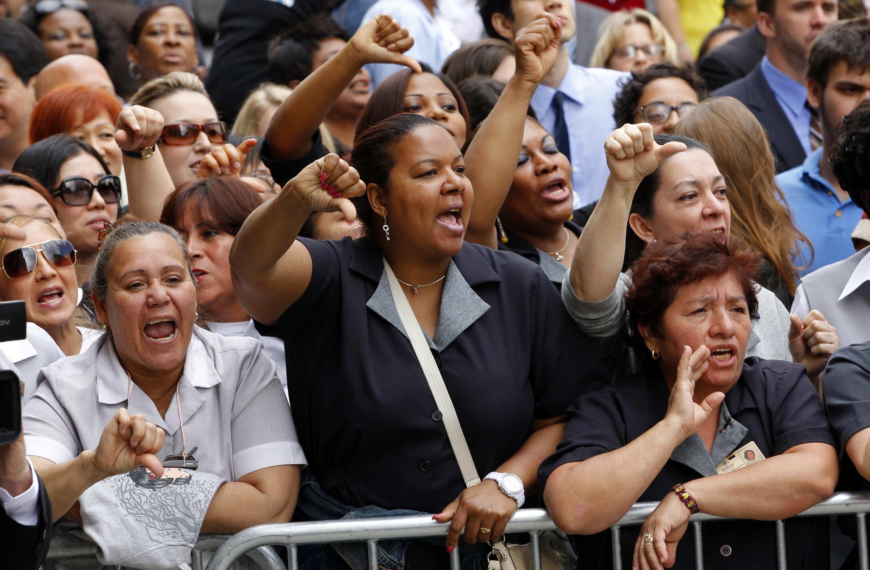 Mulheres vestidas de camareira vaiam Strauss-Kahn em sua chegada ao tribunal