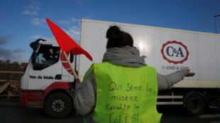 """Manifestante em estrada francesa veste colete no qual é possível ler a frase """"Quem semeia miséria, colhe miséria""""."""