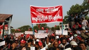 Supporters hold up signs and wave the National League for Democracy party's flag during pro-democracy leader Aung San Suu Kyi's speech at Kachin National Manu park