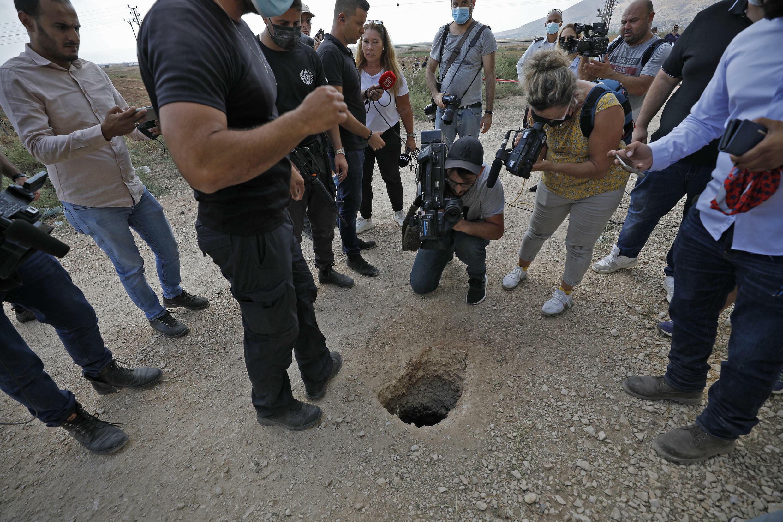 Periodistas y policías alrededor del aguejero utilizado por seis palestinos para escapar de la prisión de Gilboa, en el norte de Israel, el 6 de septiembre de 2021