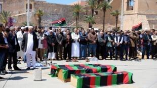 Habitantes de Tripoli recolhem-se junto dos caixões de vítimas de um bombardeamento, no 17 de Abril de 2019.
