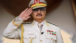 Libyan strongman Khalifa Haftar salutes during a military parade in the eastern city of Benghazi.