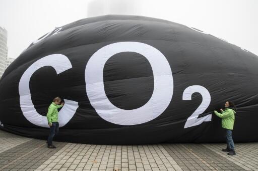 """Unos activistas de la organización ecologista Greenpeace hinchan un globo gigante en el que se lee """"CO2"""" junto a las instalaciones que acogían el Salón del Automóvil de Fráncfort, en Alemania, el 10 de septiembre de 2019"""