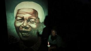 Mkazi wa Soweto akiangazia kwa mshumaa picha ya Nelson mandela iliyochorwa kwa rangi , Desemba 4 mwaka 2014.