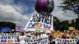 Activistas em Manila, nas Filipinas durante manifestação de 25 de novembro reclamando medidas concretas sobre o clima da COP-21 que começa segunda-feira em Paris.