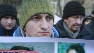 Manifestante pró-integração europeia segura cartaz com foto da jornalista Tetiana Tchornovol