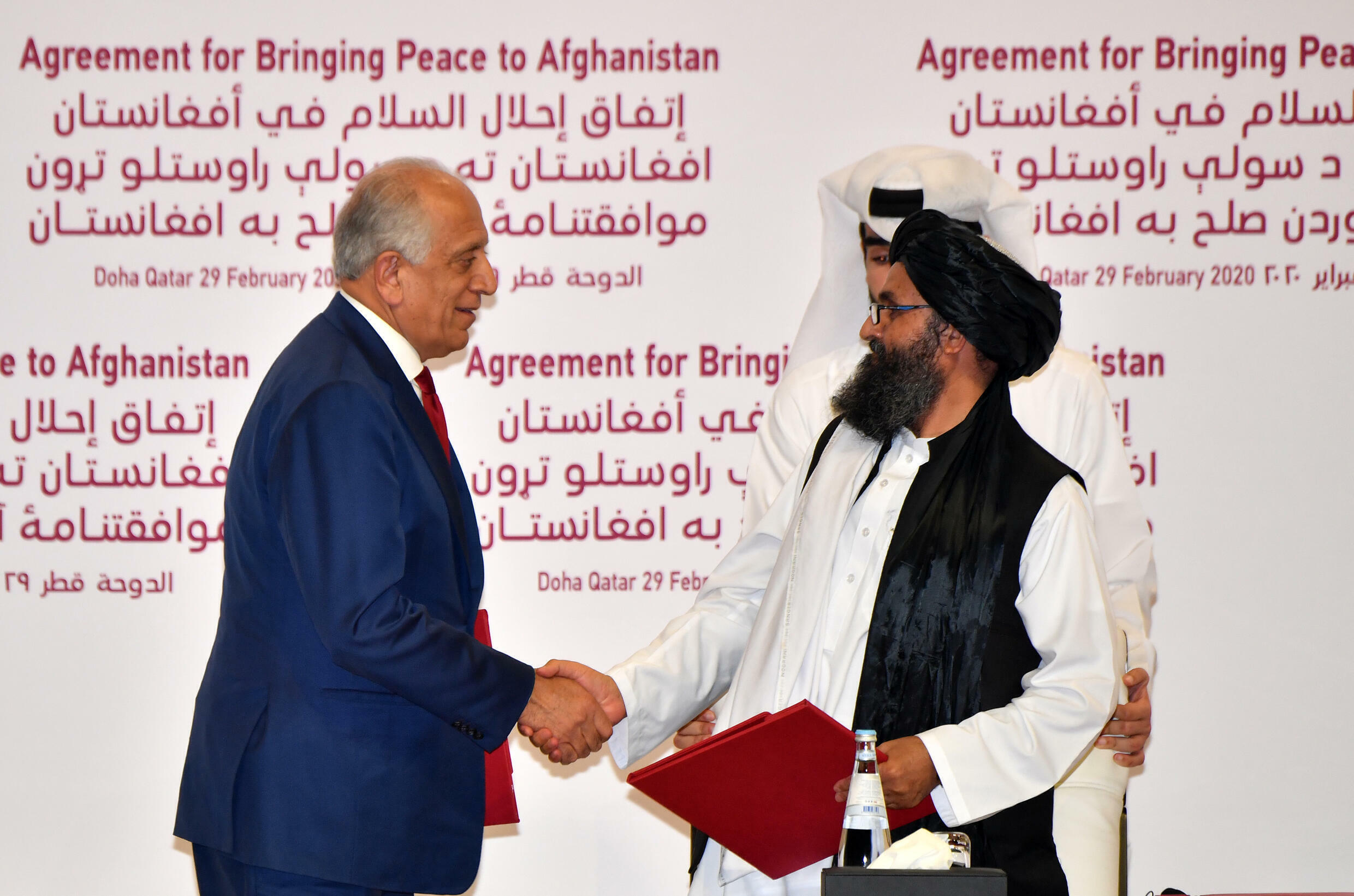 US Special Representative for Afghanistan Reconciliation Zalmay Khalilzad and Taliban co-founder Mullah Abdul Ghani Baradar shake hands after signing an agreement in the Qatari capital Doha on February 29, 2020