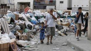 Des passants dans une rue de Beyrouth où les poubelles s'amoncellent, le 26 août 2015.