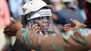 Femme portant une visière de protection face au Covid-19, à Diepsloot, près de Johannesburg.