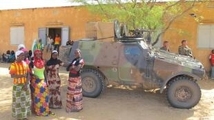 Villagers in Fafa, a village in the Gao region of northern Mali, with a French armoured car