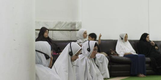 Muçulmanos no Brasil acompanham preces com fones de ouvido para compreender o que dizem os imãs.