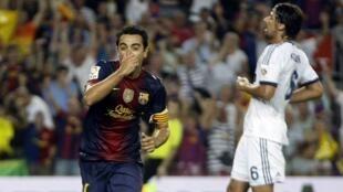 Dan wasan Barcelona Xavi yana murnar zira kwallo a ragar Real Madrid kusa da Sami Khedira  a wasan neman lashe Super Cup a Nou Camp