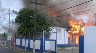 Un station de police brûle, à Kingston, où l'état d'urgence à été instauré dimanche.