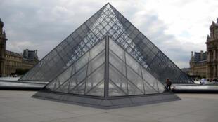 A pirâmide do Louvre é feita de vidro e metal, rodeada por três pirâmides menores, no pátio principal do Museu do Louvre.