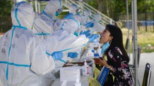 北京,6月20日,穿着防护服的医务人员对居民进行核酸检测。