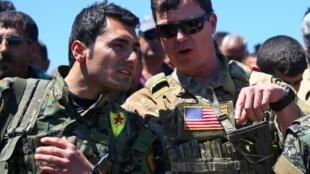 Wani sojin Amurka tare da daya daga cikin mayakan Kurdawa na kungiyar YPG a Syria.