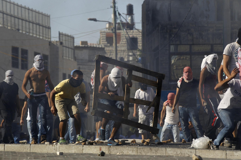 Палестинские демонстраны бросают камни в израильских полицейских во время беспорядков в арабском квартале Иерусалима Шуафат, 2 июля 2014 г.