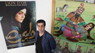 Le réalisateur iranien, Jafar Panahi, devant l'affiche d'un de ses films, «Le Cercle» pour lequel il a reçu le Lion d'or à la Mostra de Venise, à Téhéran, le 30 août 2010.