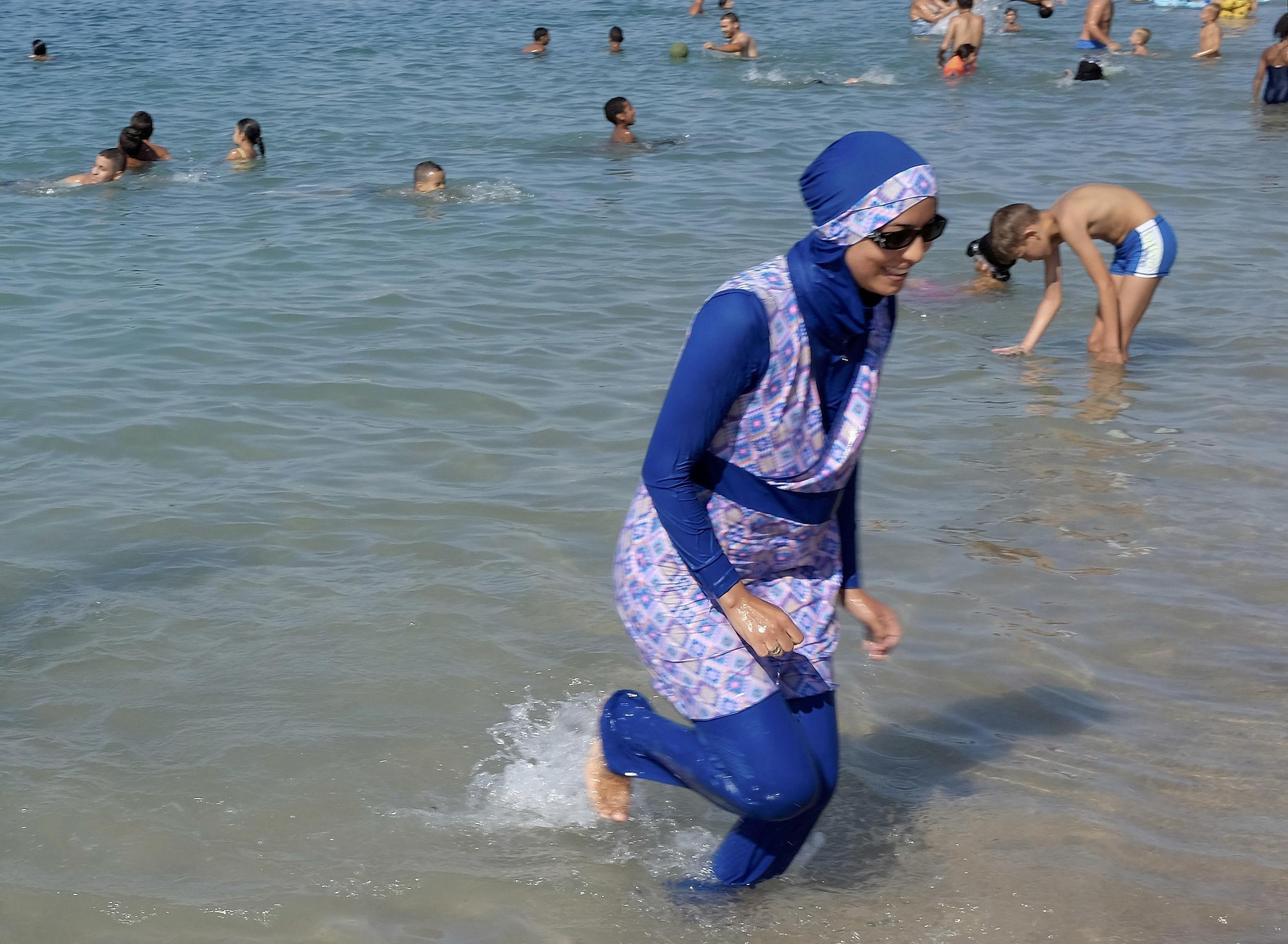 A woman wearing a burkini walks in the water on a beach in Marseille on 27 August, 2016.