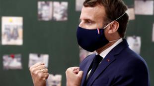Presidente Emmanuel Macron durante uma visita a uma escola, com uma máscara arvorando as cores da bandeira francesa: vemelho, azul e branco.
