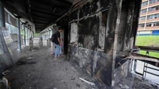 Un hombre observa daños en una estación de autobuses incendiada en Cali, Colombia, el 30 de abril de 2021, un día después de una violenta protesta contra un proyecto de ley de reforma tributaria presentado por el presidente Iván Duque.
