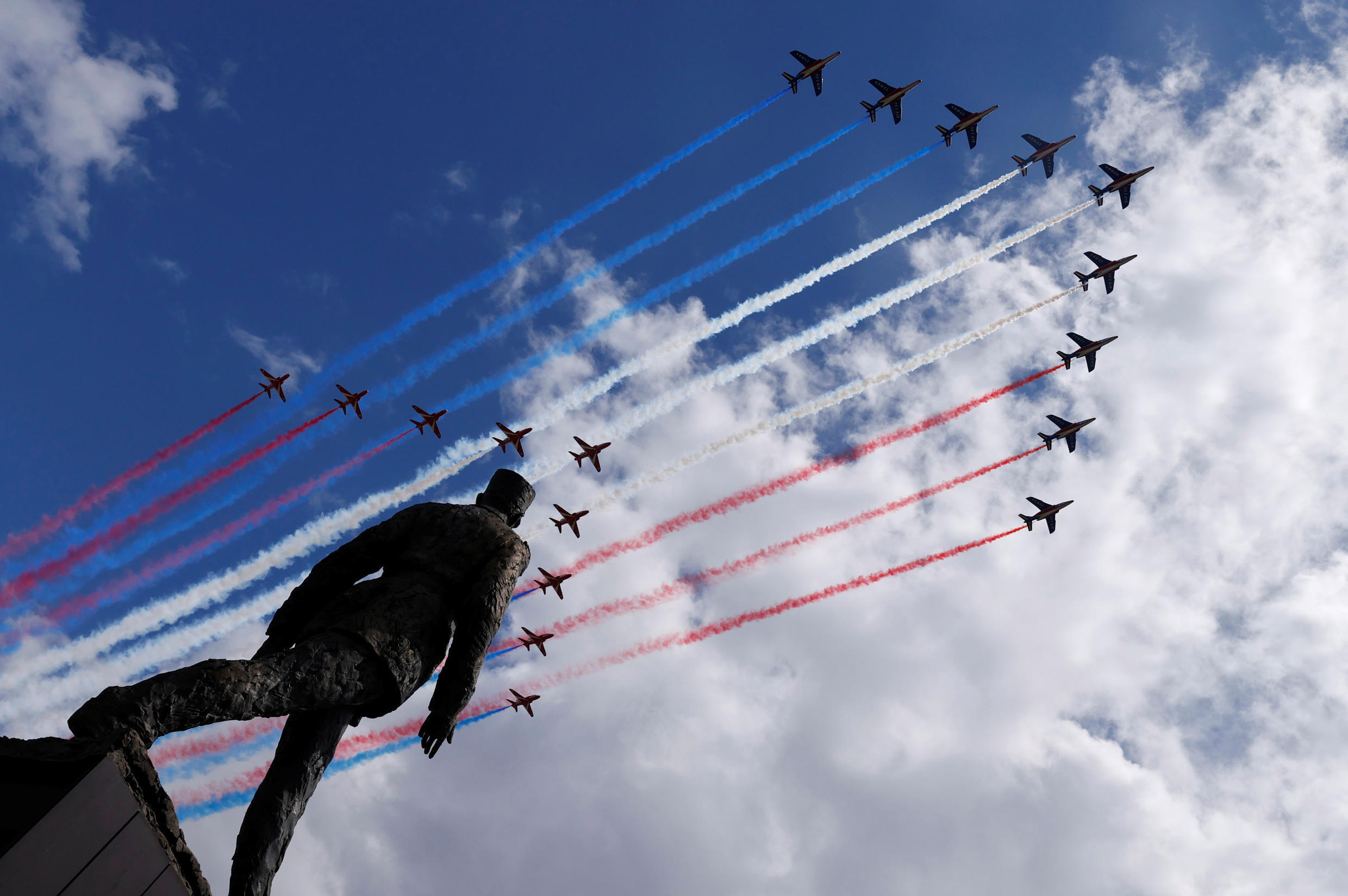 Alpha jets from the French Air Force Patrouille de France and the Royal Air Force Red Arrows fly over the statue of Charles de Gaulle on the Champs Elysees avenue to celebrate the 80th anniversary of the wartime leader's appeal to the French to resist the Nazi occupation, June 18, 2020.