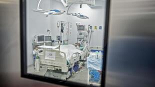 Un paciente de covid-19 es visto a través de una ventana mientras permanece en la Unidad de Cuidados Intensivos del