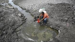 Um morador pegando água no lago Las Canoas a 59 quilômetros de Managua, Nicarágua, durante seca.
