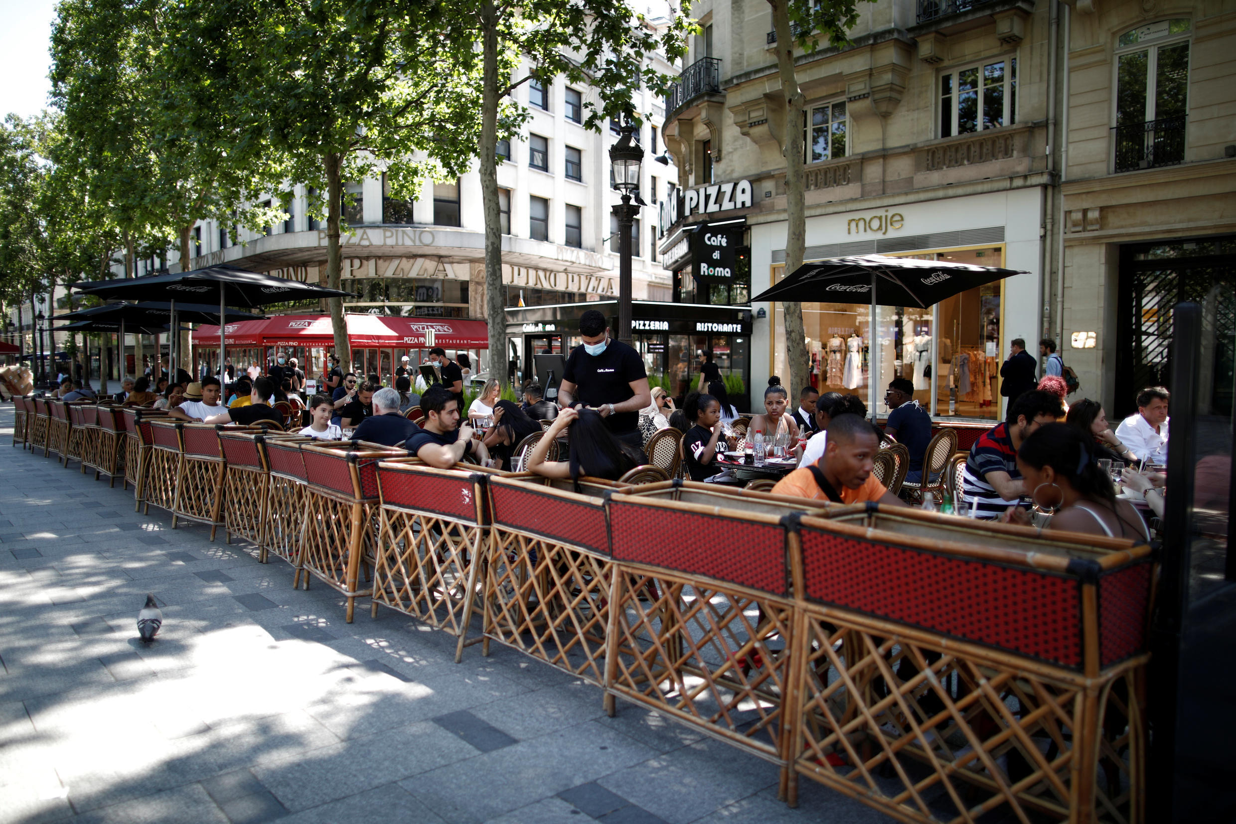 Customers have lunch on a terrace of a restaurant on the Champs Elysees in Paris on 2 June 2020.