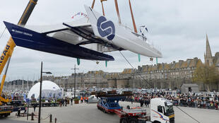 The hydrogen-powered catamaran Energy Observer while getting lowered into the sea at Saint Malo in France.