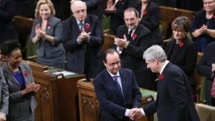 Poignée de main entre le président français François Hollande (C) et le Premier ministre canadien Stephen Harper (R) avant leur discours devant le Parlement.