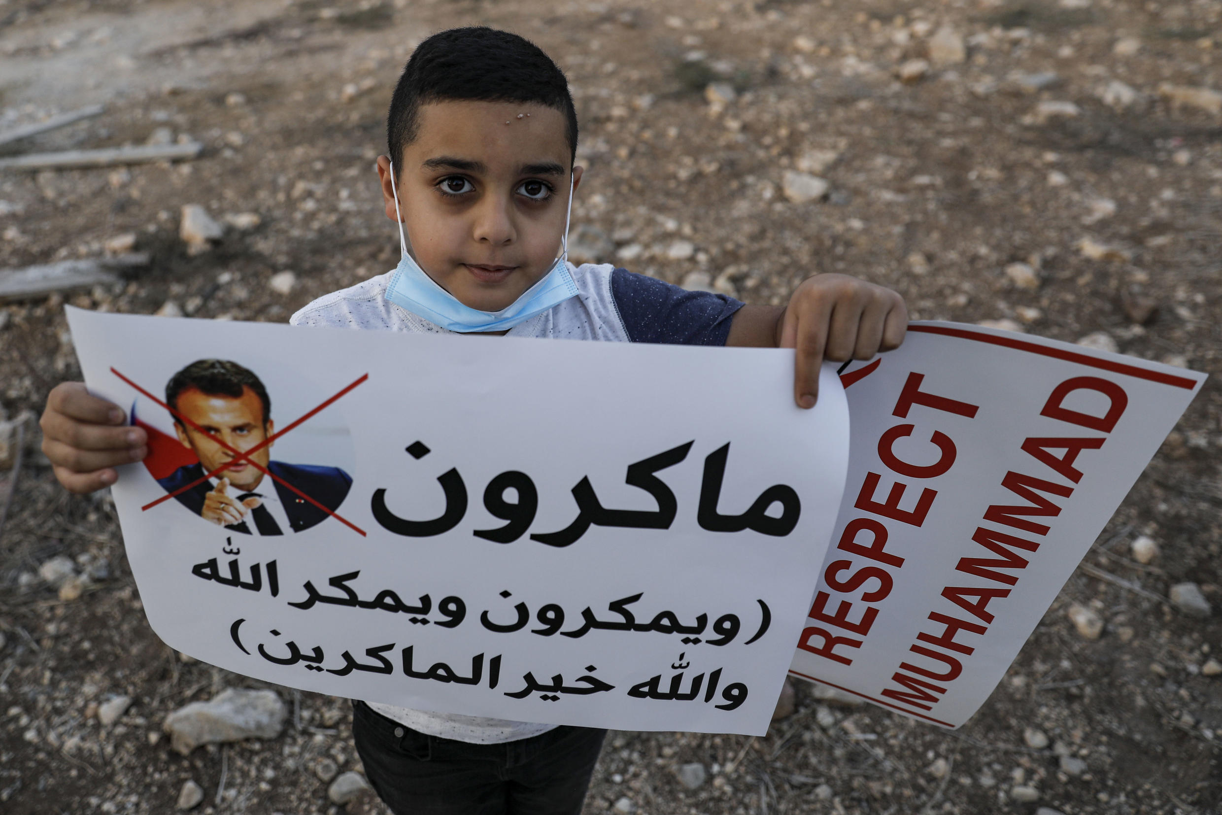 An Arab Israeli Muslim boy holds up a sign during a rally protesting against the comments of French President Emmanuel Macron over Prophet Mohammed cartoons, in the Arab town of Umm-Al Fahem in Northen Israel on October 25, 2020.