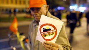 Un homme tend un tract appelant au boycott du referendum sur la question du nom de la «République de Macédoine du Nord», le 27 septembre 2018 à Skopje.